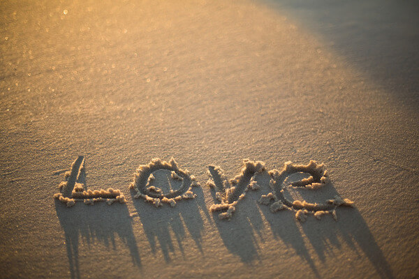 love written on the beach at the sunset